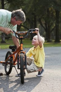 Grandfather (60s) helping grandson (5 years) with bike.