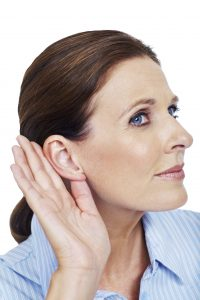 Mature woman holding her hand to her ear listening on a white background